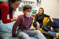 A doctor examines Christopher Serrano, 10, who is covered by the Children's Health Insurance Program, at Dell Children's Medical Center in Austin on Jan. 7, 2018. With no immigration deal in sight, Republicans are eyeing a stopgap bill to keep the government open past Friday, sweetening it with an extension of the child health program. (Ilana Panich-Linsman/The New York Times)