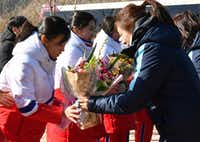 North Korean women's ice hockey players, left, are greeted as they arrive at the South Korea's national training center, Thursday, Jan. 25, 2018, in Jincheon, South Korea. Twelve North Korean female hockey players have crossed the border into South Korea to form the rivals' first-ever Olympic team during next month's Pyeongchang Winter Games. (Song Kyung-Seok/Pool Photo via AP)(Song Kyong-Seok- pool/AP)