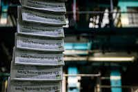 Copies of the April 7 issue of<i>The Dallas Morning News</i>are transported as printing presses roll at the North Plant in Plano.(Ashley Landis/Staff Photographer)