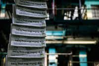 Copies of the April 7 issue of&nbsp;<i>The Dallas Morning News</i>&nbsp;are transported as printing presses roll at the North Plant in Plano.(Ashley Landis/Staff Photographer)
