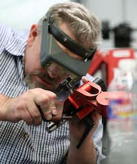 Todd Begg sands a knife at his shop in Dallas.(Rose Baca/Staff Photographer)