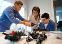 Mitch Basson lends a helping hand to his wife, Ingrid, and 17-year-old-son, Sam, as they finished constructing a Batmobile from Legos at their Dallas home. The Bassons moved to Texas from the Chicago area six months ago after reading about the 29 Acres program planned in Cross Roads.(Tom Fox/Staff Photographer)