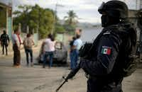 A police officer stands guard as personnel of Guerrero state attorney's office work next to a car which was found with three calcined bodies inside in the outskirts of Acapulco, Guerrero state, Mexico, on January 25, 2018.  Nearly 19,000 people have been killed due to organized crime in Mexico in 2017, the most violent year in twenty years, according to a report revealed Tuesday by the Mexican NGO Semaforo Delictivo. Guerrero is one of Mexico's poorest and most violent states, where a lucrative drug trade has flourished.(FRANCISCO ROBLES/AFP/Getty Images)