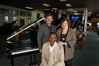 Johnnie Lindsey (seated), at Metroplex Piano with owner Darren Speir and Debbie Beach, photographed in June 2014. Lindsey donated keyboards to Beach so she could start a music school.(Evans Caglage/Staff Photographer)