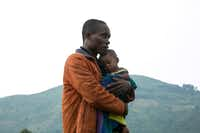 A Congolese man holds his child after he crossed the border from the Democratic Republic of Congo to be refugees at Nteko village in western Uganda.(Sumy Sadurni/Agence France-Presse)