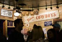 "A ""Welcome Cowboys"" sign is displayed above the bar at Gruene Hall, shown in 2015. (Ashley Landis/Staff Photographer)"