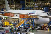 Workers on Boeing's final-assembly line in Everett, Wash., produce a 787 destined for Qatar Airways on June 5, 2015. (Mike Siegel/Seattle Times)