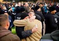 Fellow Richardson police officers console one another before a vigil held for slain Richardson police officer David Sherrard was held outside the Richardson Civic Center in Richardson, Texas, Sunday, February 11, 2017.(Tom Fox/Staff Photographer)