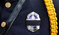 A black mourning band covers the badge of Dallas police office C. Anderson honoring Richardson police officer David Sherrard outside of Watermark Community Church in Dallas, Texas, Tuesday, February 13, 2018. (David Woo/Staff Photographer)