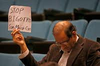 Plano resident Hasan Waqar holds up a sign while Mayor Harry LaRosiliere speaks during a news conference at the Plano Municipal Center on Feb. 14, 2018.(Jae S. Lee/Staff Photographer)