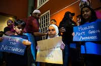 Mustafa Anas, 7, left, Rama Alkhmis, 5, and Amna Anas, 9, hold signs outside Plano's annual State of the City address on Thursday at the Courtyard Theater in Plano.(Ashley Landis/Staff Photographer)