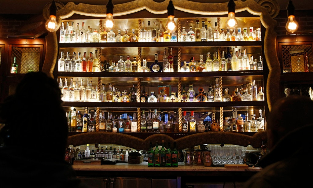 <p><span>The center section of the bar at Mexican Sugar in Plano features many different types of mezcal and tequila.</span></p>(Vernon Bryant/Staff Photographer)