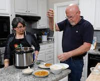 Urvashi Pitre, left, watches her husband, Roger Gorman, place spiralized cucumber noodles on a plate at their home in Keller.(David Woo/Staff Photographer)