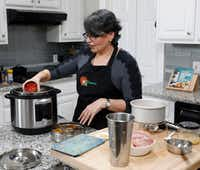 Urvashi Pitre of Keller adds a can of tomatoes to the Instant Pot while she makes butter chicken.(David Woo/Staff Photographer)