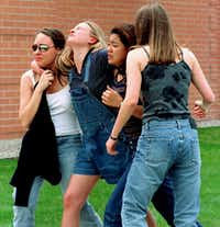 In this April 20, 1999 file photo, unidentified young women head to a library near Columbine High School where students and faculty members were evacuated after two gunmen went on a shooting rampage in the school in the southwest Denver suburb of Littleton, Colo.(Kevin Higley/AP)