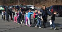 In this file photo, Connecticut State Police lead a line of children from the Sandy Hook Elementary School in Newtown, Conn. on Dec. 14, 2012, after a shooting at the school. (Shannon Hicks/Newtown Bee)