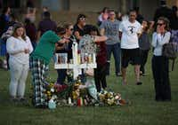 People visit a memorial at Pine Trails Park on Saturday in Parkland, Fla. Police have arrested former student Nikolas Cruz and charged him with 17 murders for the shooting at Marjory Stoneman Douglas High School on Wednesday.(Mark Wilson/Getty Images)