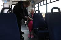 Envoy America driver Kris Werner helps Jeannyne Reston with her seatbelt on the bus at The Heritage at Twin Creeks in Allen.  The group of seniors was heading to Texas Roadhouse for lunch. (Anja Schlein/Special Contributor)
