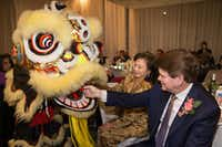 Grace McDermott watches as Arlington Mayor Jeff Williams feeds the lion a red envelope for good luck during the U.S. Pan Asian American Chamber Southwest's celebration of the Lunar New Year, held Feb. 10. (Jarvis Jacobs)