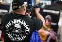 An attendee inspectss an assault rifle during the 2013 NRA Annual Meeting and Exhibits at the George R. Brown Convention Center in Houston(Justin Sullivan/Getty Images)