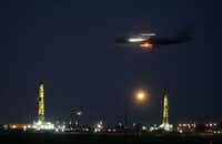 Incoming American Airlines jet with natural gas wells in the background at dusk at DFW airport. Photographed Aug. 17, 2008.(Guy Reynolds/Staff)