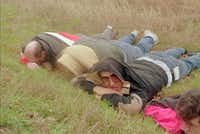 <i>Waco Tribune Herald</i> reporters Mark England (left), Tommy Witherspoon and Marc Masferrer take cover in a ditch as the gunbattle rages.(The Associated Press)