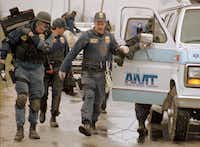 ATF agents walk alongside an ambulance filled with wounded comrades as they retreat from the Mount Carmel compound after their raid went awry.(The Associated Press)