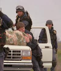 <p>ATF agents help Bill Buford away from the Branch Davidian compound on Feb. 28, 1993, after gunfire erupted as the agents attempted to execute an arrest warrant on Branch Davidian leader David Koresh and search for illegal weapons.</p>(The Associated Press)