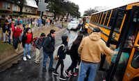 As a precaution, students from Stephen C. Foster Elementary are evacuated and loaded onto school buses following a fatal house explosion on Friday. Dallas Fire and Rescue spokesman Jason Evans said five people were transported to the hospital before sunrise after a house exploded in the 3500 block of Espanola Drive near Love Field in Dallas. (Tom Fox/Staff Photographer)
