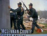 Federal agents prepare to give covering fire to others entering the compound as the raid begins.(KWTX-TV)