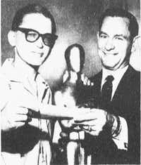 "Photo in April 13, 1963 edition of <i>The Dallas Morning News</i>: ""It was a fortunate visit John D. Monroe, left, made to the Palace Theater last week where he filled out the winning ballot in the Academy Award Sweepstakes. Monroe is shown here with his $500 cash first prize check, a 4-foot replica of Oscar and Palace manager Ted Steinberg, in that order""(Dallas News Staff Photo)"