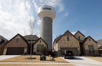 A McKinney water tower looms behind new homes on Leadville Way in fast-growing McKinney. The city's population now stands at nearly 180,000, a nearly 7 percent increase from last year and a 365 percent increase from two decades ago. (David Woo/Staff Photographer)
