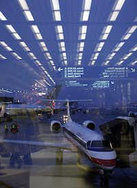 An American Eagle regional jet in front of larger American Airlines planes while the concourse is reflected in the window of Terminal 3 at O'Hare International Airport. (Brian Cassella/TNS/File)