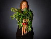 Rebecca White of A Pleasant Little Kitchen grasps a handful of vegetables she'll use to make vegetable dishes.(Tom Fox/Staff Photographer)