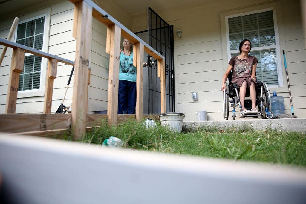 Angie Fox, who is paralyzed and uses a wheelchair, explains some of the construction problems in the home that she shares with her elderly mother, Mary Hollis, left. Among them: she says the contractor did not build a wheelchair ramp leading to the backyard.(Rose Baca/Staff Photographer)