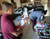 Gregory Hill holds one of his newborn triplets, Lena, while wife Kisha tends to Gemma and Gregory at their home in Fort Worth on March 7, 2018.(Rose Baca/Staff Photographer)