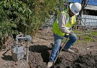 Utility worker Gerardo Esquivel worked this week to remove an old steel pipe and gas meter in a back yard on Espanola Drive in Dallas.(Jae S. Lee/Staff Photographer)