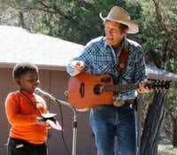 "<p><span style=""font-size: 1em; background-color: transparent;"">Samuel Bedford takes the stage to help out ""Cowboy </span><span style=""font-size: 1em; background-color: transparent;"">Bob"" Ackerman  during Cowboy Camp in Cedar Hill. About 70 kids from DISD took part in team building, story time and singing. </span></p>(David Woo/Staff Photographer)"
