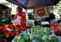Marla Baugh of Baugh Farms bags tomatoes at the McKinney Farmers Market(Anja Schlein/Special Contributor)