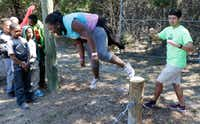 Sakia Baker tries to balance on a wire as Cameron Hernandez (right), challenger course facilitator, reacts during a teamwork exercise at Cowboy Camp.(David Woo/Staff Photographer)