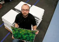 Keith Pocock, general manager of operations at GrowLife Innovations, holds luxury vinyl tile that has a photo of cannabis printed on it. Pocock developed a reflective tile that helps plants grow indoors.(Vernon Bryant/Staff Photographer)