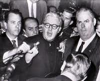 Jack Ruby's chief defense attorney, Melvin Belli (center), tells newsmen after the verdict that he will appeal.  Ruby was found guilty of murder and sentenced to death in the electric chair.  Belli charged the state with wanting a verdict regardless of due process.  At right is Belli's assistant, Joe Tonahill. (Associated Press)