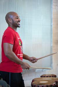 Tony Browne, director of Bandan Koro African Drum and Dance Ensemble, has a reason to smile as his group rehearses at Sammons Center for the Arts for its upcoming show, <i>Guinea Fare: Her Story, Her Ipseity</i>. After recovering from a serious ATV accident, he's back doing what he loves.(Allison Slomowitz/Special Contributor)
