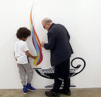 Benjamin Woods, 8, and Michael Corris examine <i>Lit</i>&nbsp;(2017), an inkjet-on-vinyl work, at Liliana Bloch Gallery in Dallas.(Nan Coulter/Special Contributor)
