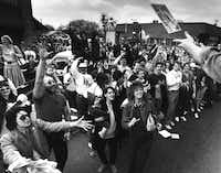 """March 14, 1987: """"A parade participant on the Fast and Cool nightclub float throws a record album into a crowd of St. Patrick's Day paradegoers on Greenville Avenue at Goodwin.""""(David Leeson/The Dallas Morning News)"""