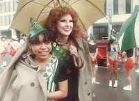 """March 17, 1984: """"The weather didn't dampen spirits Saturday as Dallasites turned out for St. Patrick's Day festivities. Anna Goergen, queen of the downtown St. Patrick's Day parade, helps Olga Rodriguez of the North Dallas Vikingettes keep warm and dry before the parade starts."""