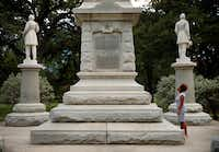 Victoria Miller of Dallas reads an inscription on the Confederate War Memorial in Pioneer Park cemetery in downtown Dallas on Aug. 23, 2017. She and the rest of her family came to see the memorial after seeing so much of the debate in the news.(Tom Fox/Staff Photographer)