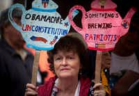 "Carlene Cahill of Petersburg, Va., holds up a set of signs she made during a tea party ""Road To Repeal Rally"" in 2012  in Washington, DC.  The group was protesting the Affordable Care Act. (Allison Shelley/Getty Images)"