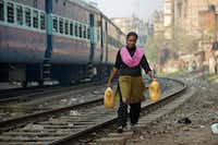 A woman who lives near the railway tracks fetches drinking water in plastic containers in Gauhati, India.(Anupam Nath/The Associated Press)