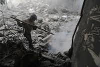 A Syrian boy puts off a fire amid destroyed buildings following government air strikes in the Eastern Ghouta rebel-held enclave of Douma, on the outskirts of the capital Damascus on March 19, 2018. At least 20 civilians have died in a resumption of bombing on Douma, the largest town in shrinking rebel-controlled pockets of Syria's Eastern Ghouta, a monitor said. The fresh bloodshed came after a week-long lull in the bombardment of Douma after negotiations between rebels and regime-backer Russia allowed medical evacuations from the town.(HAMZA AL-AJWEH/AFP/Getty Images)